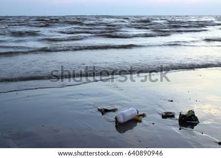 The garbage is on the beach in the background of dark sea wave in the evening