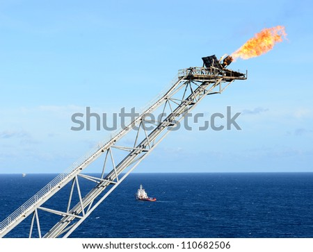The gas flare is on the oil rig platform. - stock photo