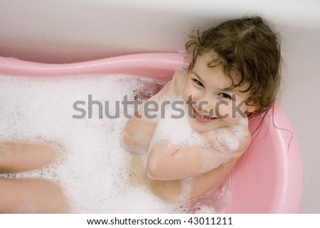 The Gentile child bathes in pink bath. She smiles.