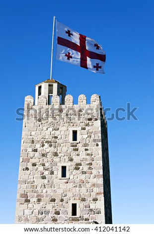 The Georgia flag on the roof of an ancient tower against the clear blue sky