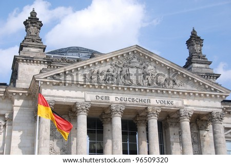 The German flag streaming in front of the German parliament building, the Reichstag at Berlin, Germany.