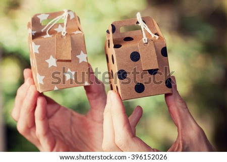 The gift in women's hand`. Surprise present for a dear person, friend, family member is always a good idea, not only on  major celebrations like Christmas, Valentines day,  Easter.  - stock photo