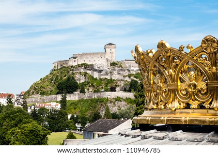 the gilded crown of the lourdes basilica and walls of the castle in the distance