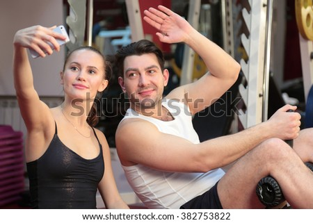 The girl and the guy doing in the gym and doing selfie