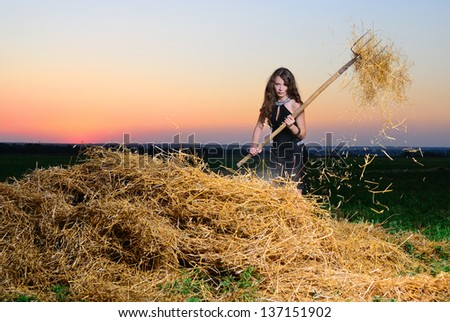 The girl at sunset with a pitchfork at a haystack - stock photo