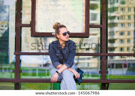 The girl at the bus stop in sunglasses - stock photo