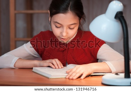 the girl at the desk reading a book by the light of the lamp - stock photo