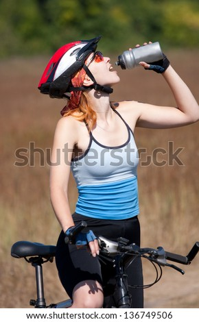 The girl by bicycle drinks water