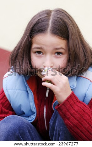 The girl child smelling a flower - stock photo