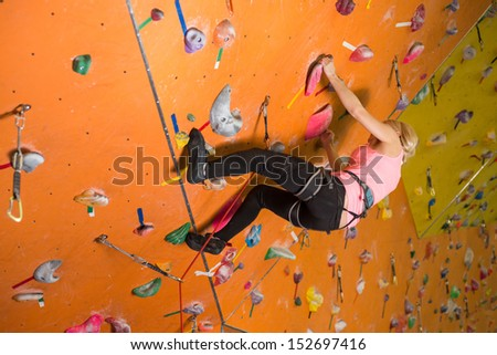 The girl climbs the steep wall on the climbing gym - stock photo