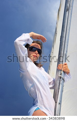 The girl costs on a yacht nose keeping for a sail during a storm also looks afar - stock photo