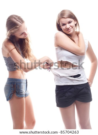 The girl cut shirt on another girl studio photography - stock photo