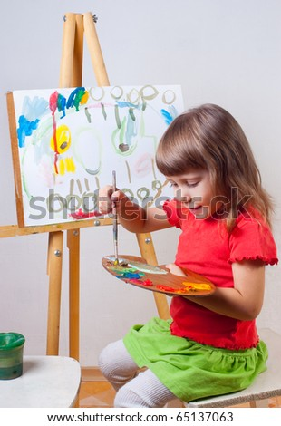 The girl draws a painting at the easel