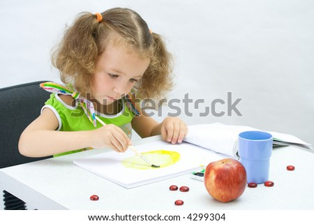 The girl draws by paints in an album - stock photo