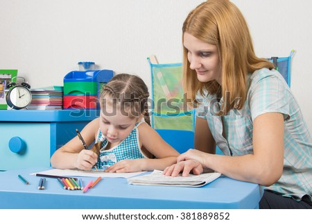 The girl draws in a notebook with a ruler, the teacher helps her - stock photo