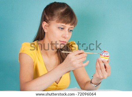 The girl draws patterns. Painting eggs for Easter - stock photo