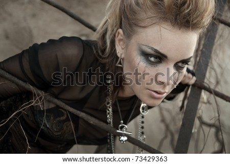 The girl dressed and make-up in rock style. Make-up after tears. She is upset and thoughtful, does not know what to do. - stock photo