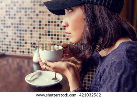 the girl drinks coffee at a roadside cafe. Warm Colors Toned - stock photo