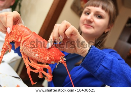 The girl eats a lobster in a restaurant - stock photo
