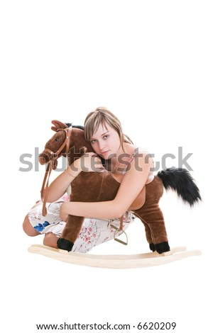 The girl embraces the toy horse - stock photo