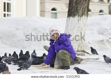The girl feeds pigeons with pearl barley. - stock photo