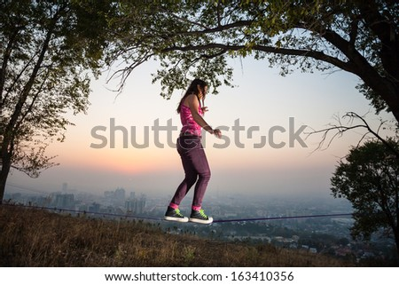 The girl goes and shows tricks on tightrope at sunset and the city slack-line - stock photo
