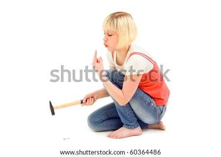 The girl hammers itself hammers in a nail