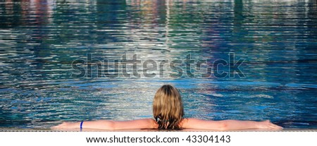 The girl has a rest in pool. The rear view - stock photo