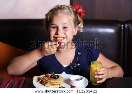 The girl has breakfast in a cafe