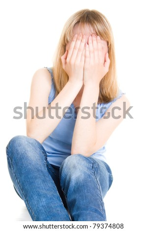 The girl hid her face in her hands. - stock photo