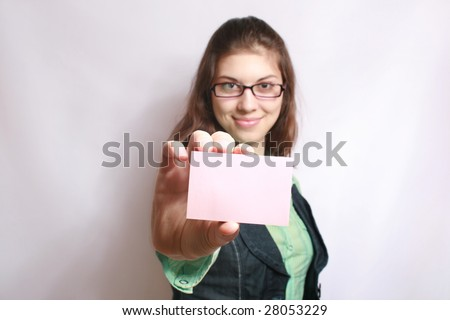 The girl holds a card in the hand extended forward.