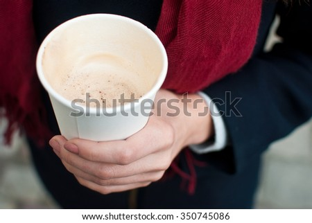 The girl holds the paper cup of coffee with milk - stock photo