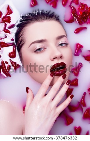 The girl in a bath with rose petals. The water with the milk. Red lipstick and red nails. The girl's face. - stock photo