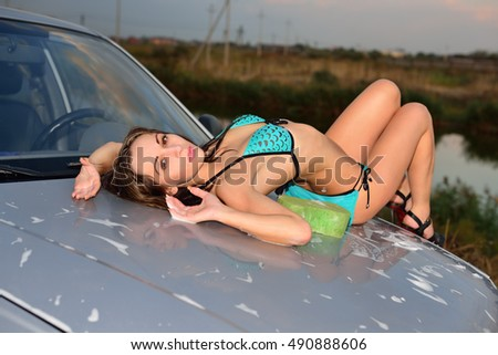 The girl in a bathing suit lying on the hood of car and  washes it