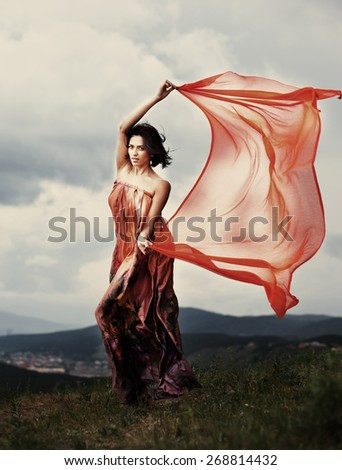 The girl in a beautiful dress in the wind