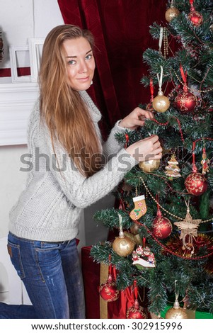 The girl in a Christmas tree interior , fireplace , red and white color