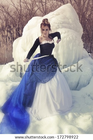 The girl in a dress and a icicle on a winter landscape - stock photo