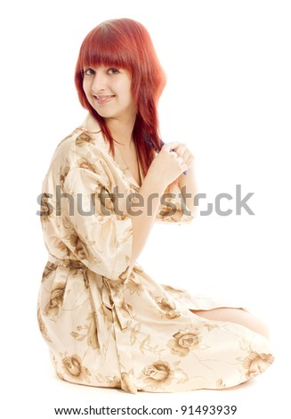The girl in a dressing gown combs hair - stock photo