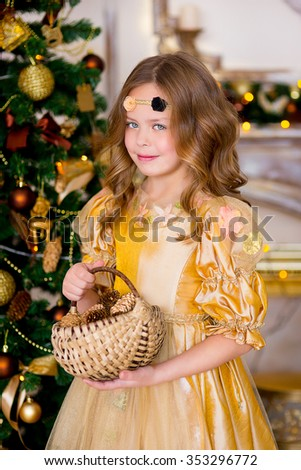 the girl in a gold dress costs with a basket of cedar cones near a New Year tree