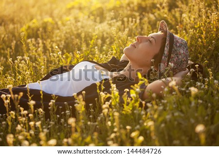 The girl in a hat dremet among wildflowers at sunset - stock photo