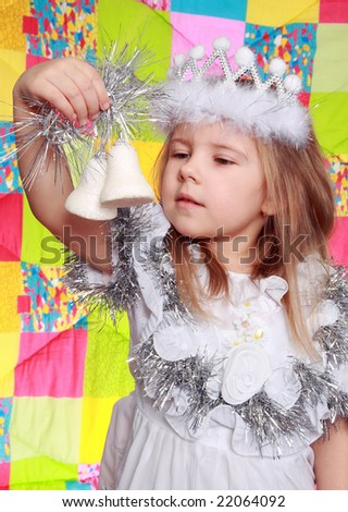 The girl in a New Year's dress looks at a fur-tree`s  toy