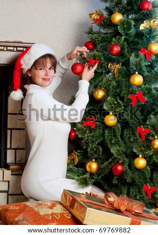 The girl  in a Santa hat near the Christmas tree in a house interior