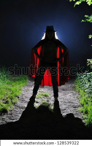 The girl in a suit of the superhero in the night wood - stock photo