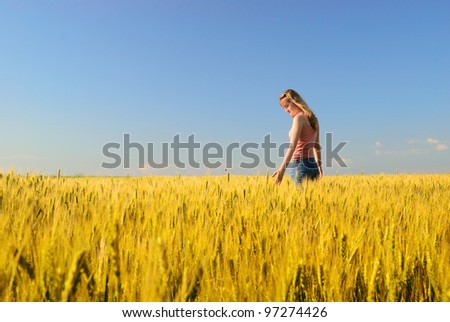 The girl in a wheaten field looks at wheat - stock photo