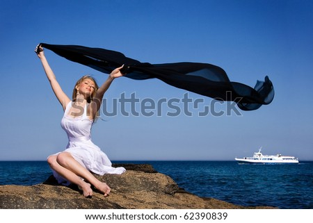 The girl in a white dress holds a scarf on a wind