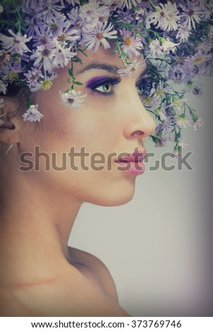 The girl in a wreath of purple daisies