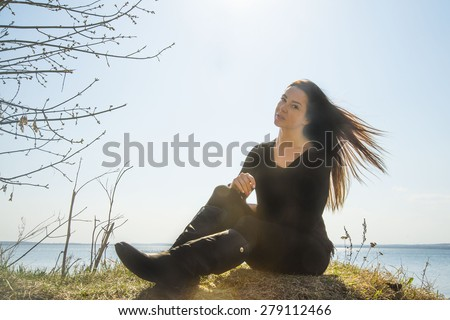 The girl in black clothes at coast sea against spring blue sky Sun shine rays on hairs Windy warm weather Cute stylish woman wear black leather high boots and sit on fresh spring grass  - stock photo