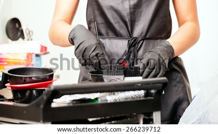 The girl in black gloves hairdresser mixes hair dye. In the beauty salon. - stock photo