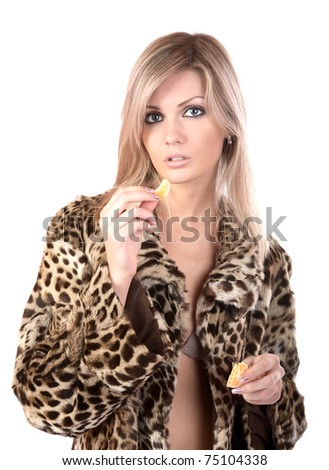 The girl in  fur coat holds in hand  tangerine on  white background