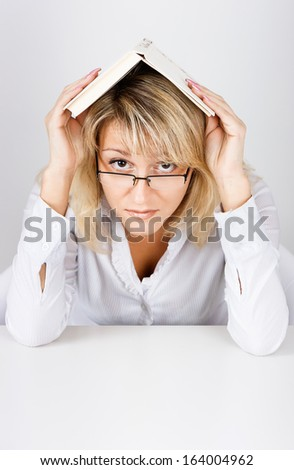 The girl in glasses looking out from under the book - stock photo